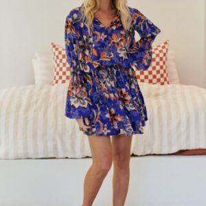 Vestido corto azulón fruncido a la cintura y vuelo en la falda, cuello alto , que puede cerrarse con una cinta.